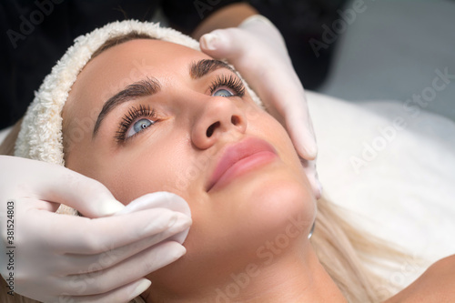 Young woman in a beauty salon. The beautician makes a facial cleansing procedure. Focus on eyes