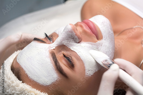Applying a mask to the face in a beauty salon. Cosmetologist and procedure for rejuvenation and moisturizing.