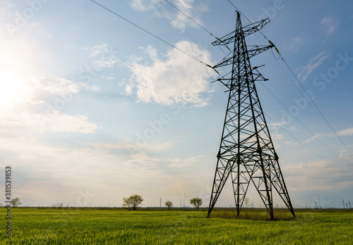 Fototapeta High voltage lines and power pylons and a green agricultural landscape on a sunny day