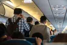 People Are Standing In An Airplane Cabin Before Disembarking