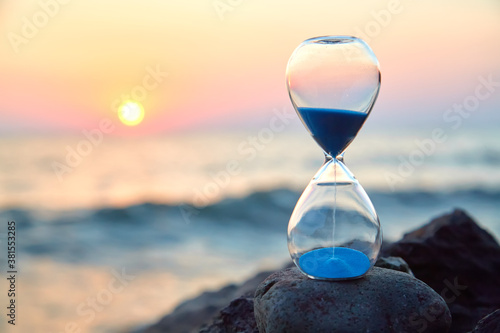 Obraz na plátně Hourglass with sand standing on rock