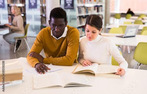 Portrait of couple of adult students studying together in public library Tapéta, Fotótapéta
