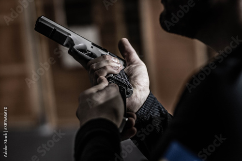 Fotografia The shooter infects the pistol, the athlete inserts the magazine into the pistol