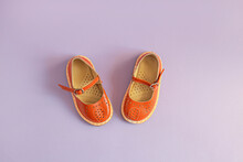 Bright Orange Kids Shoes On Lilac Background With Copyspace. Baby Clothes Concept. Top View, Flat Lay
