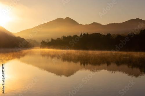 朝焼けの光景が映り込む静かな湖面