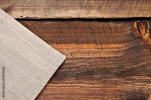 Fragment naciągniętego płótna na blejtram, na tle starych, chropowatych desek.