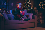 Full size photo of amazed elf sit couch watch three dimensional film with pop corn box in evening christmas x-mas decor house indoors