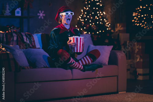 Fototapeta Full size photo of amazed elf sit couch watch three dimensional film with pop corn box in evening christmas x-mas decor house indoors obraz