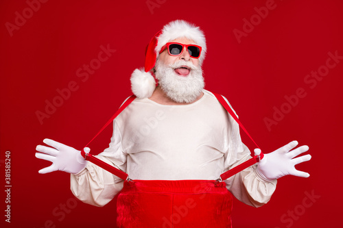 Fototapeta Portrait of his he nice handsome cheerful cheery bearded Santa pulling suspenders having fun fooling event newyear good mood celebratory isolated bright vivid shine vibrant red color background obraz
