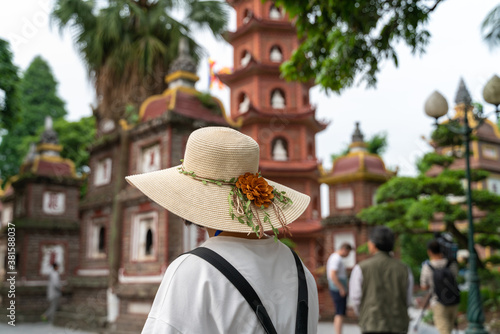Fotografering Close-up female tourist visiting Tran Quoc ancient pagoda, the oldest Buddhist t