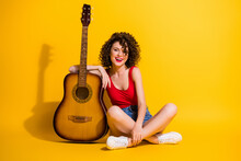 Portrait Photo Of Young Girl Musician With Curly Hair Holding Keeping Hand Touching Guitar Instrument Sitting Down Isolated On Vivid Yellow Color Background