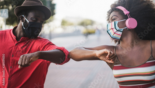 Fotografía African people wearing face masks while bumping their elbows instead of greeting