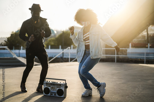 African people dancing outdoor listening music wearing face masks - Young friend Fotobehang
