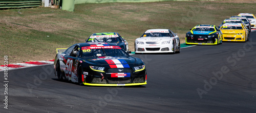 Euro Nascar racing Ford Mustang car in action at turn during race