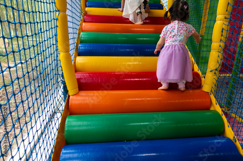 Fotografie, Obraz Colorful stairs in children play house, with child legs climbing up closeup