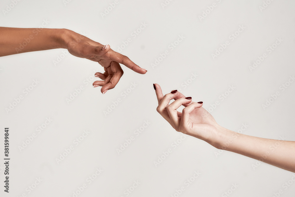 Fototapeta Close up of two hands of diverse women reaching for each other isolated over grey background