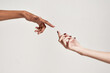 Close up of two hands of diverse women reaching for each other isolated over grey background