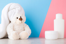 Smiling Lovely White Teddy Bear Sitting On Shelf At Light Blue Pink Wall. Towel On Head. Closeup. Shampoo Bottle And Cream Jar For Children. Pastel Color. Front View.