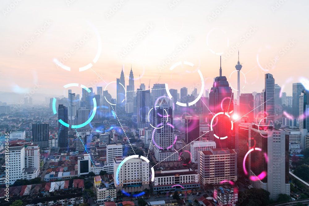 Fototapeta Hologram of abstract technology glowing icons, panoramic cityscape of Kuala Lumpur at sunset, Malaysia, Asia. The concept of worlds technological changes. Double exposure.