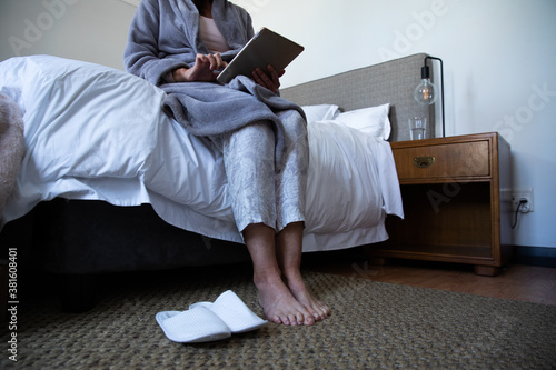 Mid section of senior woman using digital tablet in bed at home