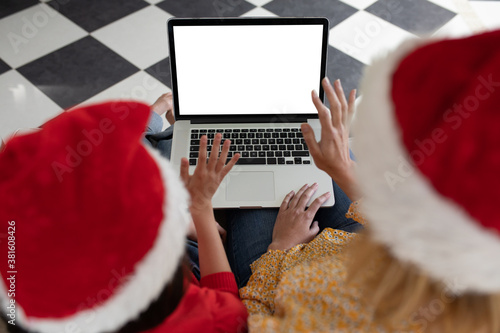 Mother and daughter in Santa hat using laptop at home