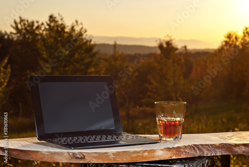 Glass with drink and laptop on a background of greenery and nature. Whiskey on an old wooden board. Sunset in summer. The concept of remote work and freelance. Rest and work in the summer.