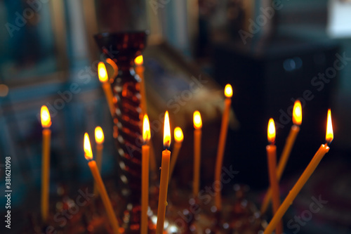Sticks of wax with a wick lighting inside the church Wallpaper Mural