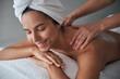 Professional masseuse massaging female back in spa salon