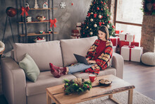 Photo Of Pretty Lady Sit Sofa Hold Laptop Legs Typing Wear Plaid Red Sweater Socks Jeans In Decorated X-mas Living Room Indoors