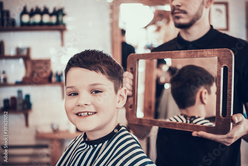 Boy sits in a chair with a new haircut and smiles.