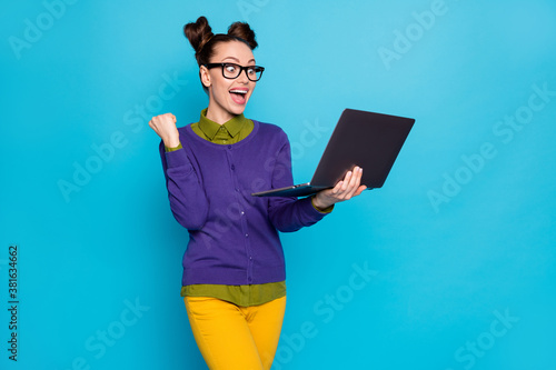 Portrait of her she nice attractive smart clever cheerful girl holding in hands laptop celebrating win winner isolated bright vivid shine vibrant blue green teal turquoise color background