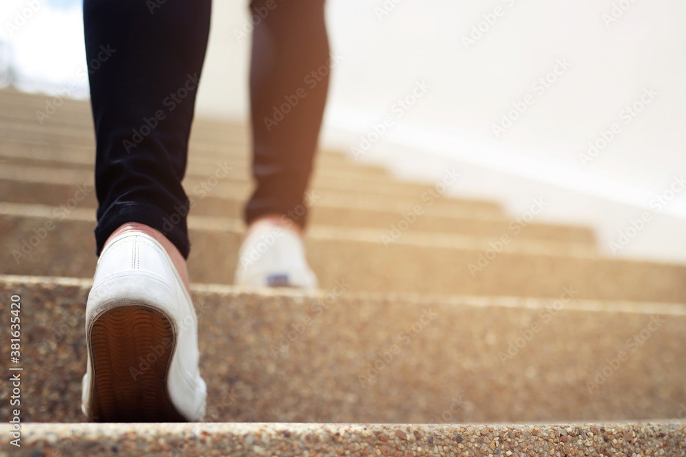 Fototapeta stairway. Close up legs and shoes sneakers of young woman one person walking stepping going up the stairs in modern city, success, grow up.