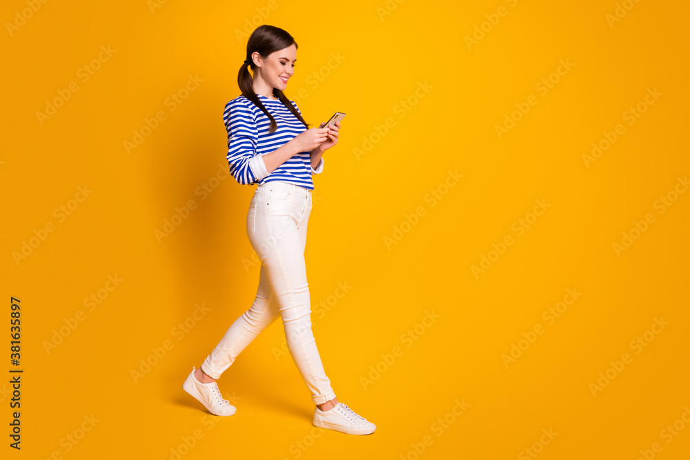 Fototapeta Full size profile side photo of positive girl use cellphone have social media communication chilling wear white clothes shoes isolated over bright shine color background