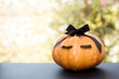 Halloween pumpkin with make up eyelashes and black bow. Holiday season concept.