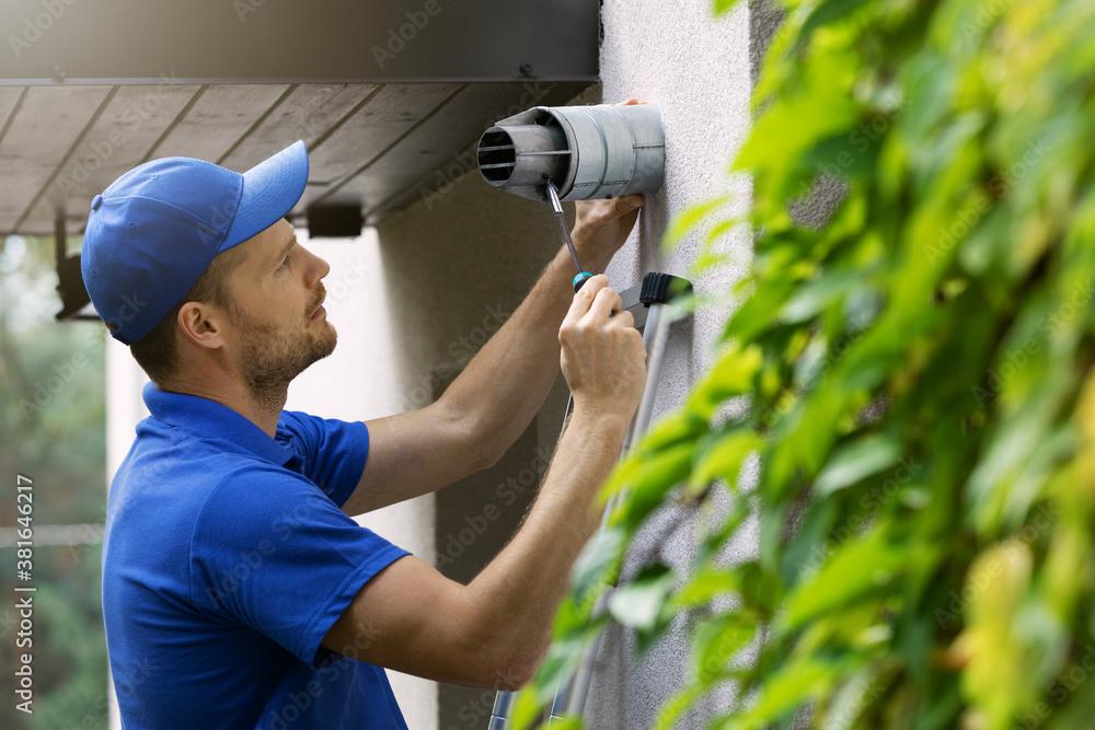 Fototapeta hvac service worker doing maintenance and repair of central gas heating boiler flue chimney on house exterior