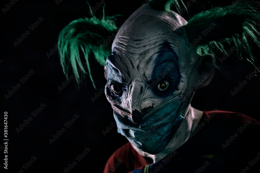 Fototapeta disturbing evil clown wearing a face mask