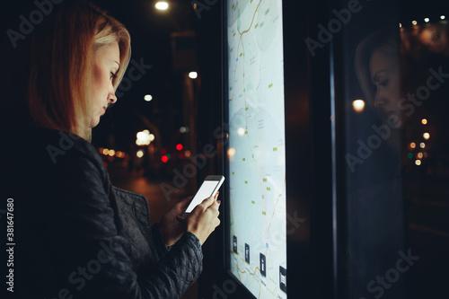 Fotomural Woman using cellphone near kiosk on street