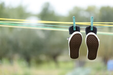 Black Sneakers On A Rope Are Drying. Black Sneakers.