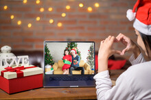 Young Smiling Woman Wearing Red Santa Claus Hat Making Video Call On Social Network With Family And Friends On Christmas Day.