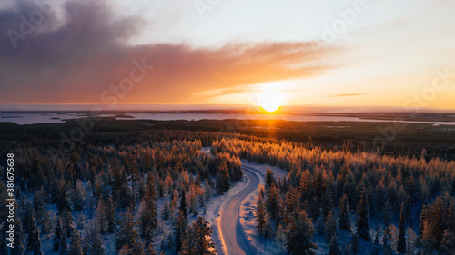 Fototapeta Aerial view from drone of snowy pines of endless coniferous forest trees in Lapland National park, bird's eye scenery  view of natural landmark in Riisitunturi on winter season at sunset golden light obraz