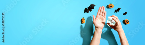 Applying sanitizer gel with Halloween theme - healthcare and hygiene concept