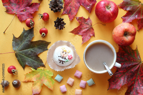 Cake with colorful candies, a Cup of cocoa and autumn leaves on a yellow background, top view