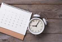 Close Up Of Calendar And Alarm Clock On The Wooden Table, Planning For Business Meeting Or Travel Planning Concept