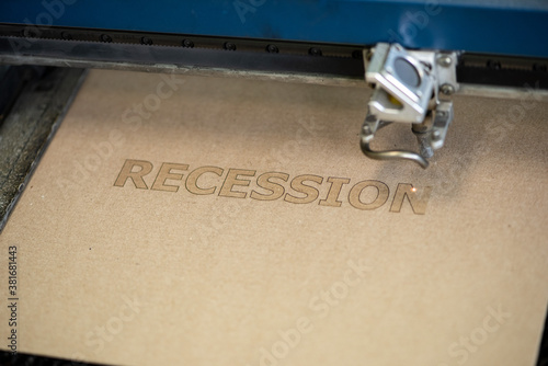 Industrial laser engraving word recession on a cardboard, close up view Canvas Print