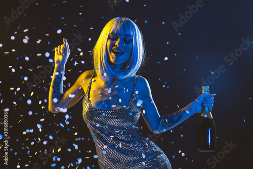 Woman In Dress With Confetti And Champagne Standing Against Black Background - 381685036