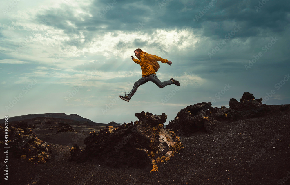 Fototapeta Hiker man jumping over the mountain. Freedom, risk, success and challenge. Focus on man