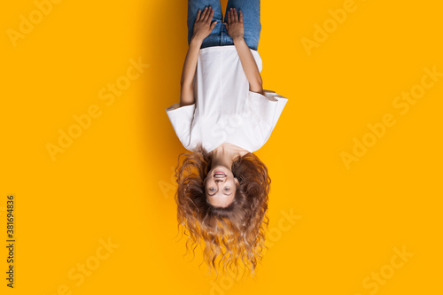 Fototapety, obrazy: Upside-down photo of a blonde lady in jeans and white t-shirt smiling at camera and advertising something