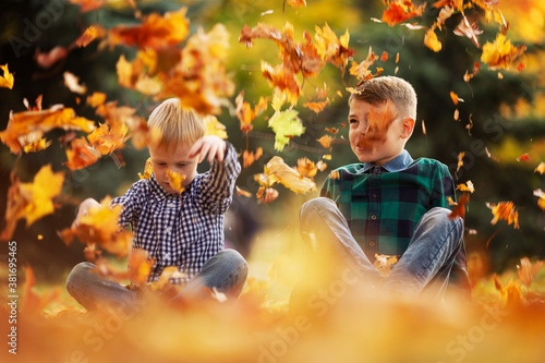Fototapeta Boys friends 7 and 10 years old sit on the ground in the park and play with autumn leaves
