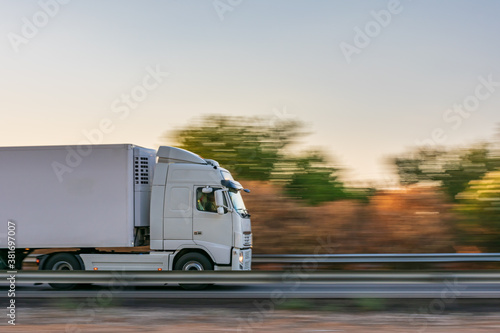 Fotografie, Obraz Refrigerator truck driving fast on the highway