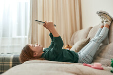 A Small Cute Girl Playing Games On A Tablet Lying On A Sofa With Her Feet Up And Gumshoes On